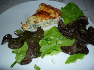 Cheese and broccoli quiche served with salad leaves and spring onions